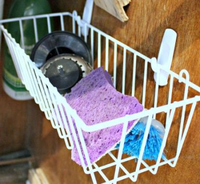 Use hooks to hold a basket under the sink to hold sponges